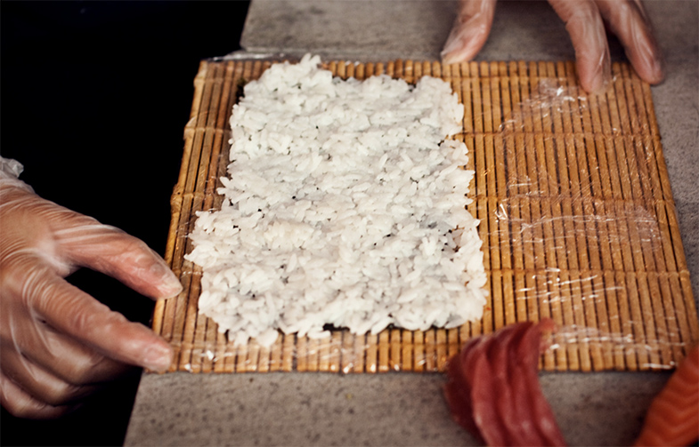 Sushirijst verspreiden over sushimatje